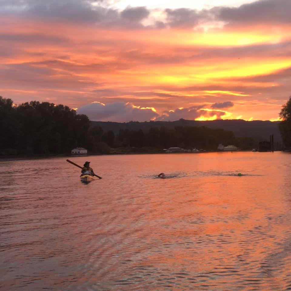 Cindy swimming with paddler at sunset